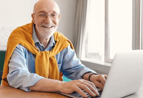 Man sitting working on his laptop smiling