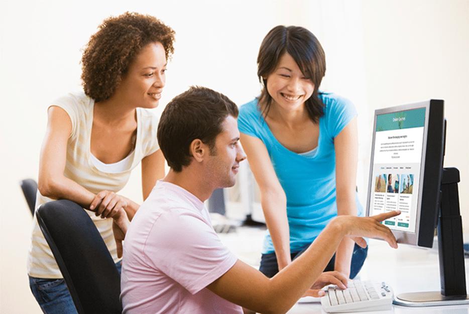 Three adults smiling looking at a computer