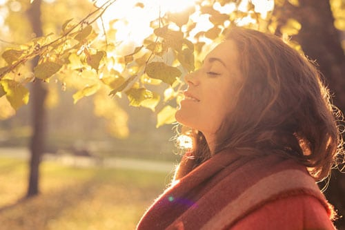 Understanding anxiety - lady smiling with her eyes shut in an autumn setting