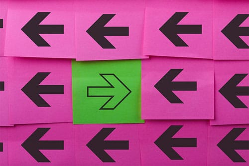 Pink posted note arrow display, with one green arrow facing the opposite direction - breaking the cycle of depression