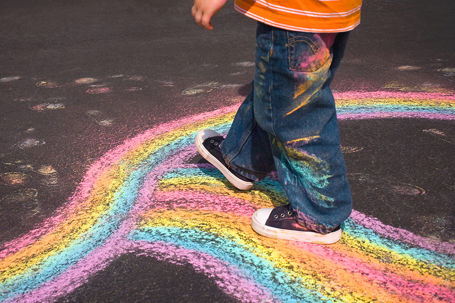 Child walking over a chalk rainbow - improving children's challenging behaviour