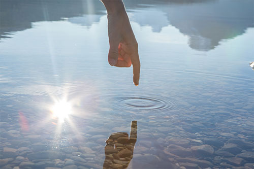 Refection of a persons finger rippling the water - creativity
