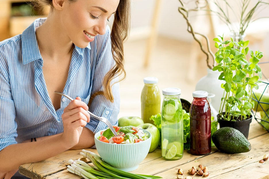 Lady sitting at a wooden table smiling eating salad - the mind-body connection