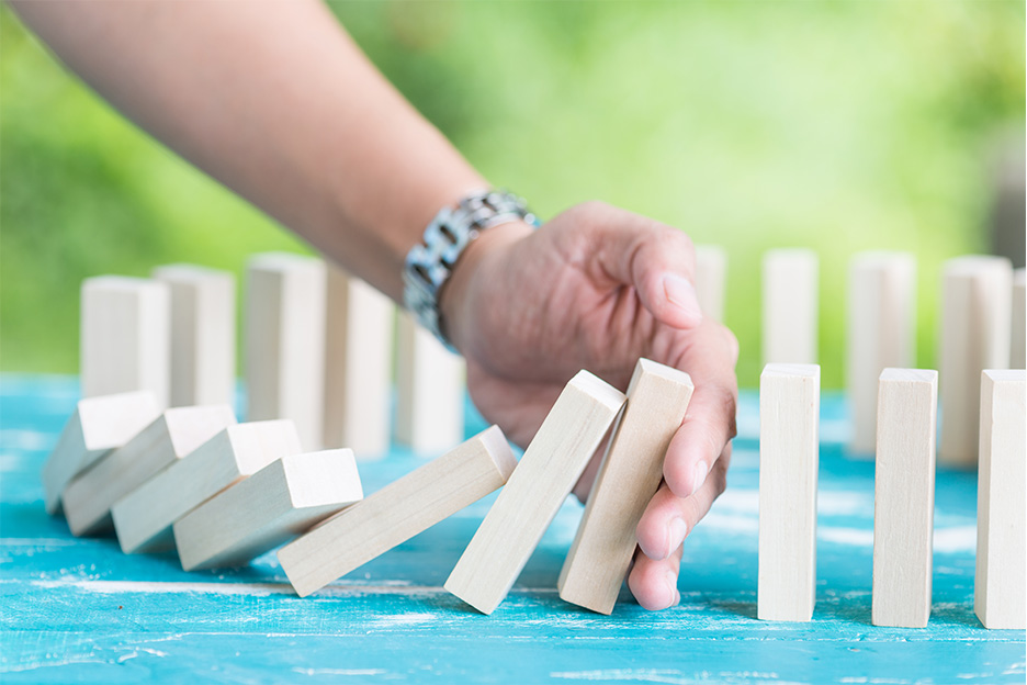 A hand preventing wooden dominos falling, symbolising stopping addictive behaviours