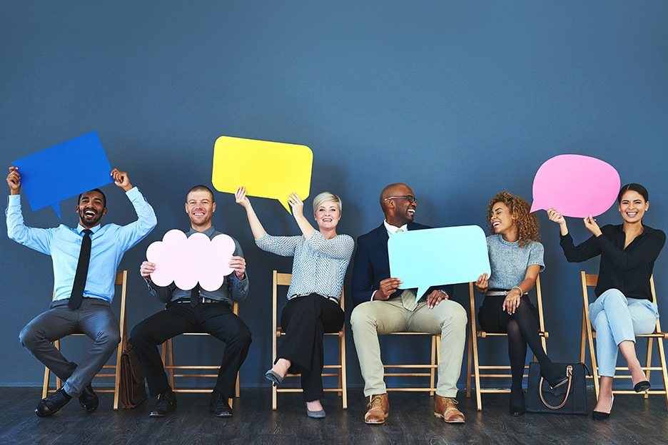 People holding different coloured speech bubbles demonstrating the power of language