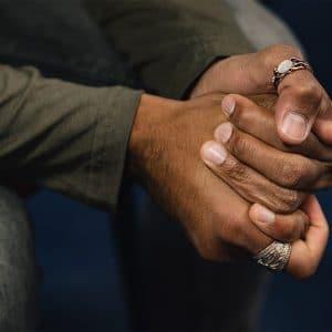 Man clutching his hands symbolising trauma for rewind technique